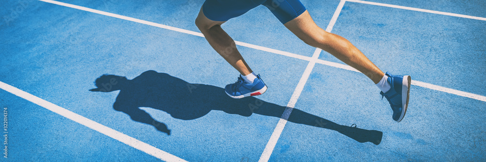 Fotografie, Obraz Sprinting man runner sprinter athlete running shoes and legs on track and field lane run race competing fast panoramic banner background