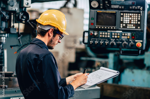 Fototapeta young profession technician engineer operate heavy machine to automated CNC in factory, worker with check list. obraz