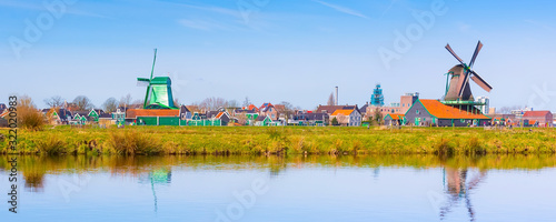 Obraz Zaanse Schans, Netherlands panoramic view of windmills and houses in traditional village in Holland, reflection in lake, blue sky, copy space - fototapety do salonu