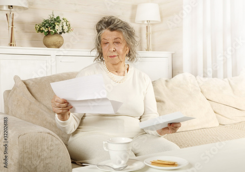 Obraz An old woman reads a letter sitting on a sofa - fototapety do salonu