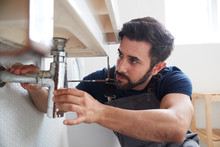 Male Plumber Working To Fix Le...