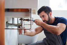 Male Plumber Using Wrench To F...