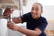 Portrait Of Female Plumber Working To Fix Leaking Sink In Home Bathroom
