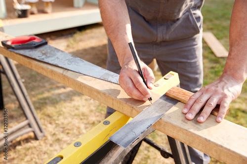 Obraz na plátně Close Up Male Carpenter Measuring Wood Using Set Square Outdoors