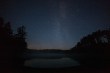 One Million Stars Over The Lake At Night. Long Exposure. Trail From A Flying Satellite. Milky Way