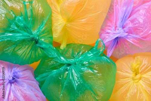 Green, yellow and violet plastic garbage bags full of air on orange background, horizontal flat lay conceptual shot