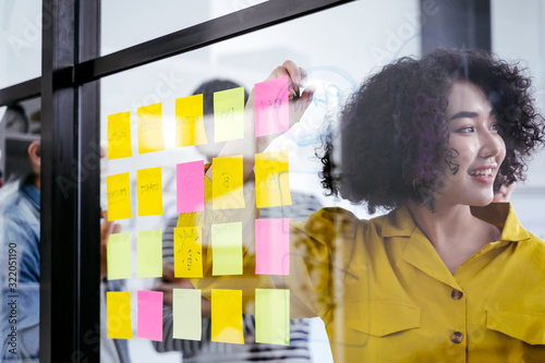 Obraz Young creative team use post it notes to share idea sticky note on glass wall. and working design planning and Brainstorming concept. Business woman and Asian business people meeting at modern office - fototapety do salonu