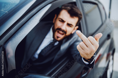 Leinwand Poster Rude caucasian bearded businessman driving his car and showing middle finger to other drivers