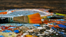 Paint Brush On A Paint Splattered Pallette.