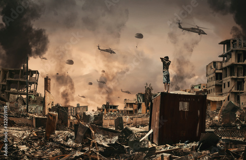 Fotografie, Obraz Homeless little boy watching Helicopters and soldiers in sky in destroyed and bombarded city between smoke