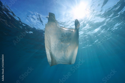 Photo Plastic pollution in ocean, a white plastic bag drifts underwater with sunlight