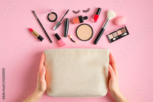 Fototapeta Female hands holding makeup bag with cosmetic beauty products over pink background. Flat lay, top view obraz