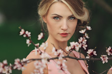 Portrait Of Young Beautiful Blonde Woman In Pink Dress Near Blooming Tree With White Flowers On A Sunny Day. Spring, Girl Near A Flowering Tree