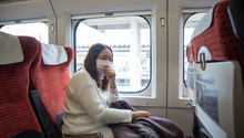 COVID-19 Virus Concept, Traveler Woman Wears Medical Mask To Protect Against Coronavirus On Public Transport Station.