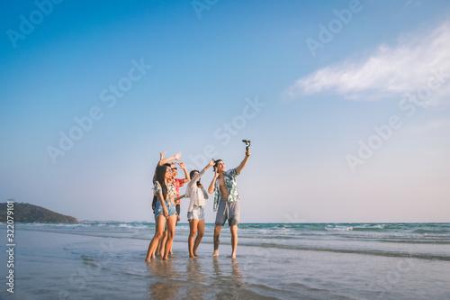 Fototapeta A group of happy friends having enjoy playing selfies on the beach amid the blue sky. obraz na płótnie