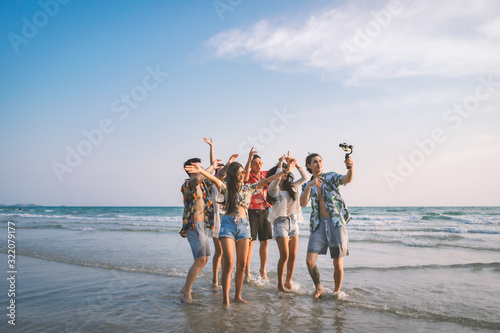 Obraz A group of happy friends having enjoy playing selfies on the beach amid the blue sky. - fototapety do salonu