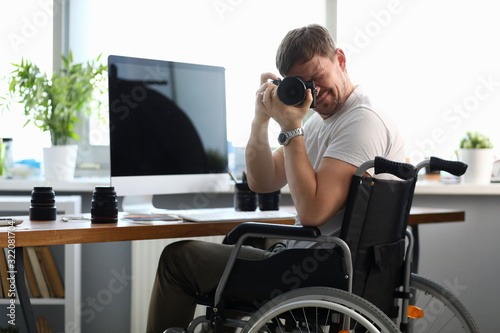 Obraz Male disabled photographer holds camera in his hands and takes picture portrait. Striving for a goal and self-sufficiency concept. Strong life position - fototapety do salonu