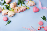 Pink eustoma flowers, pink ribbons and macaroons on a blue background in flat lay style. Spring flowers for valentines day, Mothers Day and 8 March