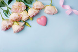 Beautiful pink eustoma flowers and pink heart with ribbon on a blue background in flat lay style. Beautiful spring card for Valentine's Day, March 8 and Mother's Day
