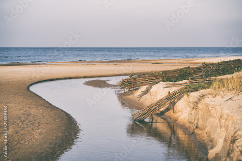 A river in sand dunes flows into the sea Wallpaper Mural