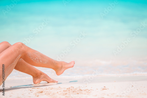 Fotografering Woman's feet on the white sand beach in shallow water