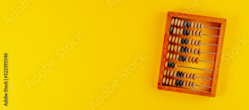 Old wooden abacus isolated on yellow background Wallpaper Mural