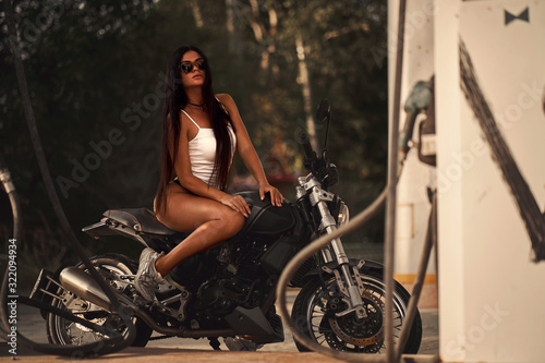 Photo Sexy fit woman with a black motorcycle in cafe racer style