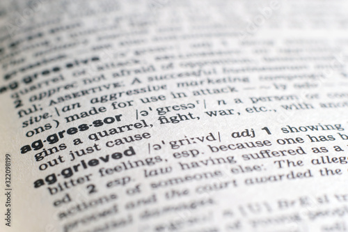 Photo A close-up on a word Aggressor in English dictionary (selective focus)