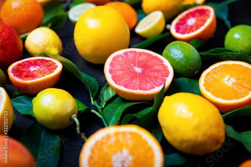 Photo Bunte Zitrusfrüchte mit Orangen, Zitronen, Pink Grapefruit und Limetten auf schw