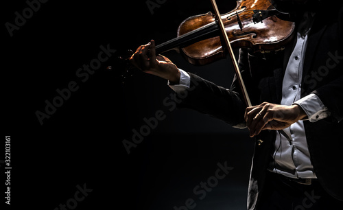 Fotografie, Obraz The violinist in a tailcoat plays the violin on a dark background