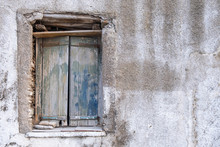 Old Double Closed Wooden Shutters. Rusty Hinges On Peeled Planks,  Stones Keep The Window Shut. Wall Blank And Faded. Copy Space.