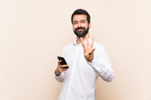 Young Man With Beard Holding A Mobile Happy And Counting Three With Fingers
