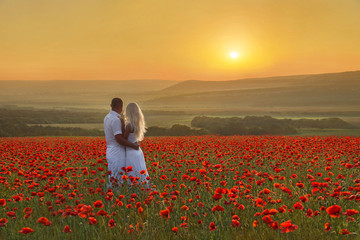 Panel Szklany Romantyczny Loving couple hug one another during romantic date in marvellous spring poppy field with bright sunset above forest and mountains. People in wild nature horizontal background.