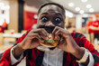 canvas print picture - A portrait of young african man eating a burger in street food cafe. Fast food eating time.