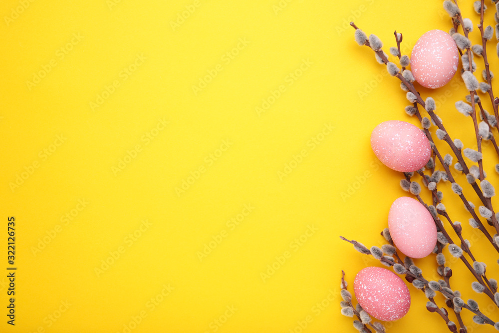 Fototapeta Pink easter eggs and willow branches on yellow background