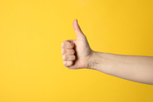 Female Thumbs Up On Yellow Background, Space For Text