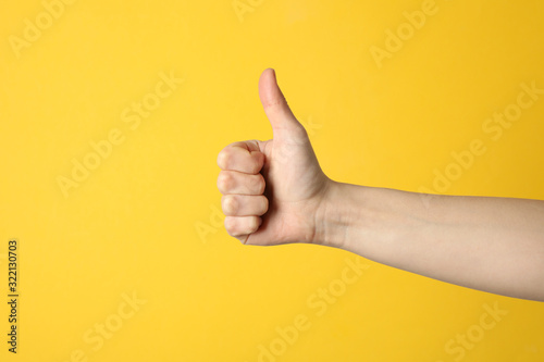 Fototapeta Female thumbs up on yellow background, space for text obraz