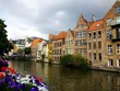 canvas print picture - Buildings surrounded by the river and flowers under a cloudy sky in Ghent in Belgium