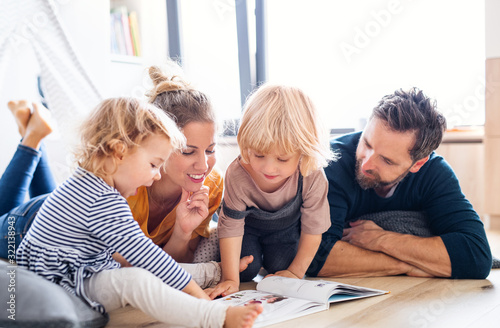 Young family with two small children indoors in bedroom reading a book. - 322138943