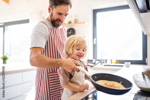 Fototapeta A side view of small boy with father indoors in kitchen making pancakes. obraz