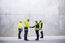 A Group Of Engineers Standing On Construction Site, Shaking Hands.