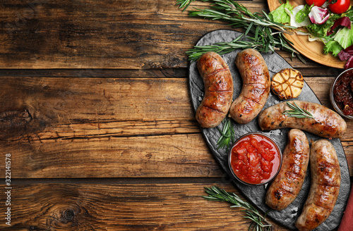 Tasty grilled sausages served on wooden table, flat lay Fototapete
