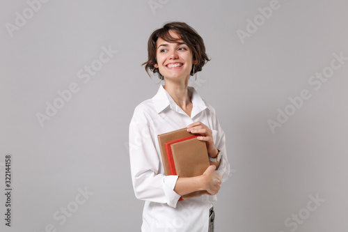 Smiling young business woman in white shirt posing isolated on grey background studio portrait. Achievement career wealth business concept. Mock up copy space. Holding books, notebooks, looking aside.