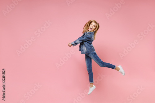 Obraz na plátně Pretty little blonde kid girl 12-13 years old in denim jacket isolated on pastel pink wall background children studio portrait