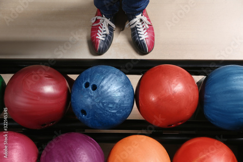 Fototapeta Person in bowling shoes near rack with balls, top view obraz