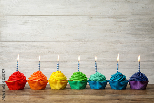 Delicious birthday cupcakes with burning candles on wooden table Wallpaper Mural
