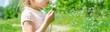 Leinwanddruck Bild - girl blowing dandelions in the air. selective focus.