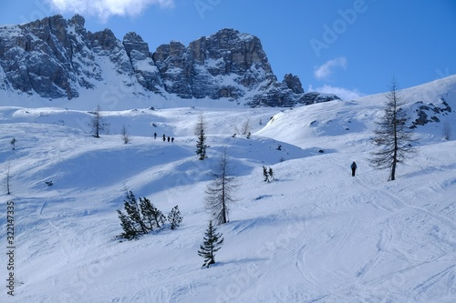 Photo A group of skiers going on backcountry skis through snowy high mountains on a sunny day