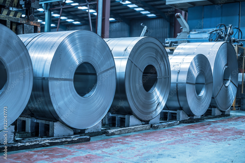 Fototapeta Industrial background. Big size steel coil stored inside industrial warehouse, blue toned image .
