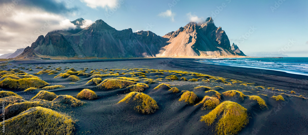 Fototapeta View from flying drone. Stunning autumn scene of Stokksnes cape with Vestrahorn (Batman Mountain) on background. Panoramic Icelandic view of black sand dunes with fresh green grass.